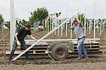Foto: vidiPhoto<br /> <br /> RESSEN - Op een ongebruikelijk tijdstip in het seizoen en met behulp van de modernste technieken en twee loonwerkers, worden zaterdag bij fruitteler Nico van Olst uit Ressen (gem. Lingewaard) 1150 betonpalen geplaatst voor 7000 nieuwe appelbomen. De plekken waar de bomen (6000 elstar en 1000 delbar) komen zijn vooraf uitgelijnd middels GPS-co&ouml;rdinaten, waardoor een tractor met GPS-systeem op exact de goede plek de gaten voor de palen en bomen boort. Vervolgens worden direct de betonnen palen geplaatst en in de grond getrild. Deze moderne wijze van aanplant scheelt dagen werk en wordt in de fruitteelt steeds vaker toegepast. Normaal gesproken worden jonge bomen in de rustige herfstperiode aangeplant. In de praktijk blijkt dan echter dat door de kou -en vraat van konijnen- relatief veel bomen dood gaan. Van Olst probeert het nu in het voorjaar met bomen die een lange tijd in de koelcel hebben gestaan en door de warmte buiten een versnelde groeistoot krijgen.