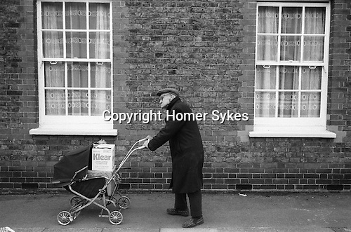 Old age pensioner pushing shopping home in a pram. Battersea London UK