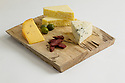 Cheese board with three cheeses, salami and olives