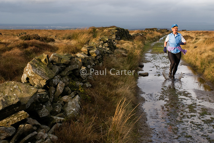 Woman running along a footpath on Wheelton Moor, near Brinscall, Lancashire