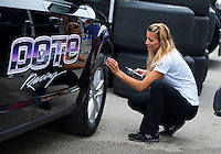 Apr 26, 2015; Baytown, TX, USA; NHRA top fuel driver Leah Pritchett Black Magic Tire Color onto the tires of her tow vehicle during the Spring Nationals at Royal Purple Raceway. Mandatory Credit: Mark J. Rebilas-
