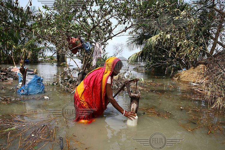 A woman collects water from a tap. There are severe clean water shortages as floodwater becomes stagnant and polluted, contaminating existing water supplies. Thousands of people were displaced in Shyamnagar Upazila, Satkhira district after Cyclone Aila struck Bangladesh on 25/05/2009, triggering tidal surges and floods..