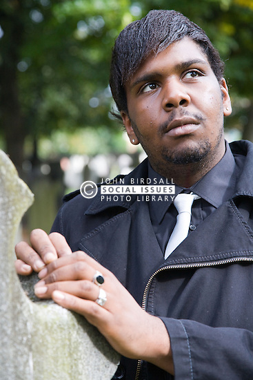 Young man standing beside a grave stone in a graveyard,