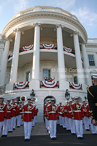 United States President Barack Obama and First Lady Michelle Obama wave from the South Lawn balcony of the White House to military families gathered for July 4th festivities, as the President's Own Marine Band stands below, Sunday, July 4, 2010..Credit: Martin H. Simon - Pool via CNP