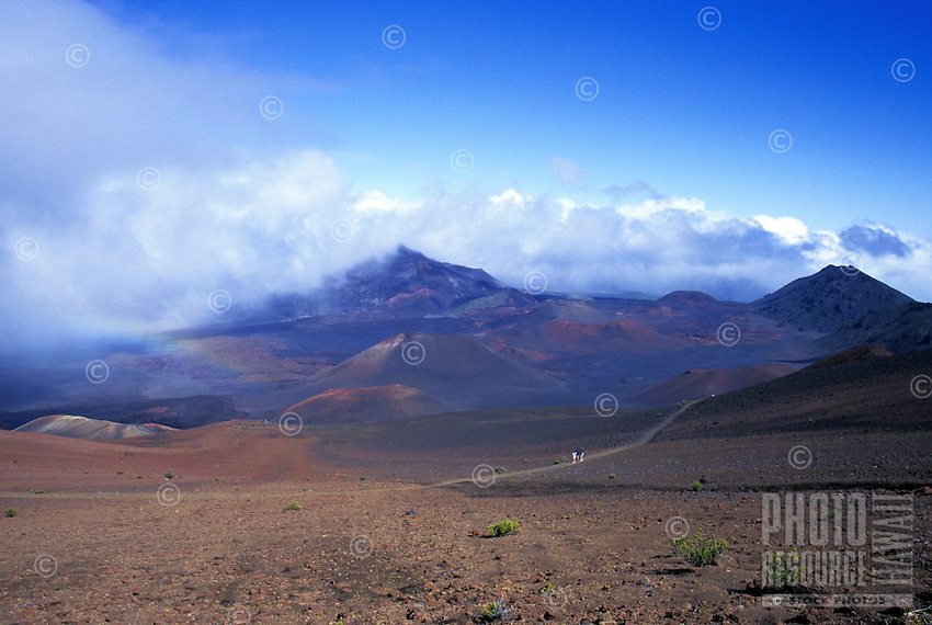 A sliver of light illuminates hikers in the barren landscape surrounding the Sliding Sands Trail at Haleakala National Park