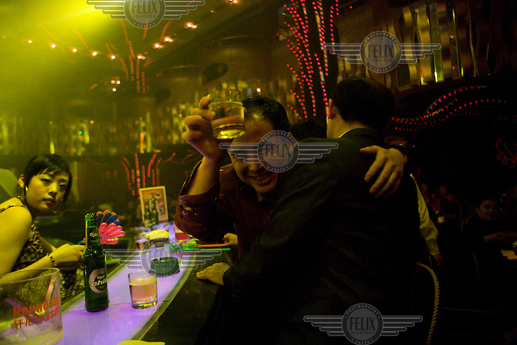 A man holds up a drink in a nightclub in Chengdu.