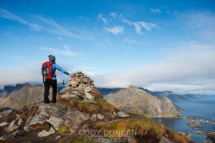Female hiker enjoys spectacular view over mountains and fjords from Reinebringen, Lofoten islands, Norway