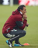 Italy coach Cesare Prandelli crouches down as he watches training ahead of tomorrow's Group D match vs Uruguay