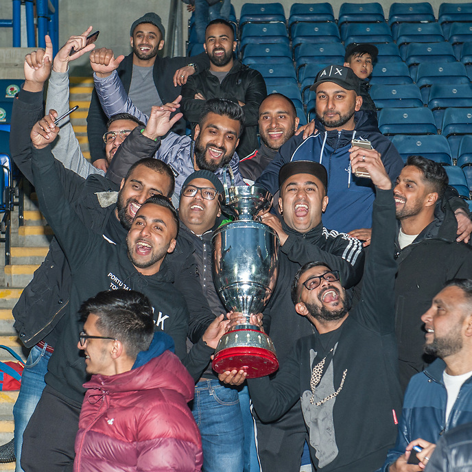 Coppice United fans celebrate with the Asian Image cup following the AMT Lawyers Asian Image Cup Final at Ewood Park, Blackburn on Friday 11th May 2018.