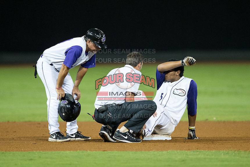 Winston-Salem Dash manager Tim Esmay (10) looks on as trainer Josh Fallin checks on the left ankle of Cleuluis Rondon (5) after he twisted it at second base during the game against the Myrtle Beach Pelicans at BB&T Ballpark on August 20, 2015 in Winston-Salem, North Carolina.  The Dash defeated the Pelicans 5-4 on a walk-off wild pitch in the bottom of the 9th inning.  (Brian Westerholt/Four Seam Images)