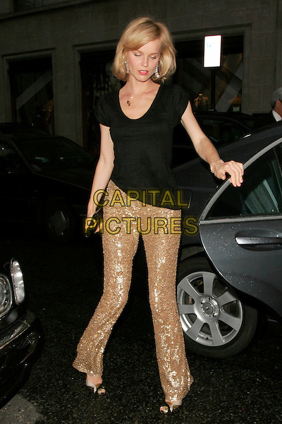 EVA HERZIGOVA.Flagship store launch party, Michael Kors boutique, London, England. .April 27th, 2009 .full length black top gold sequins sequined trousers leg up car peep toe shoes.CAP/AH.©Adam Houghton/Capital Pictures.