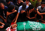 Palestinian mourners at a mosque gather around the bodies of Mousa Abu Muamer, 56, left, and his son, Saddam, 27, right, who were killed in an overnight Israeli missile strike at their house in the outskirts of the town of Khan Younis, southern Gaza Strip, Monday, July 14, 2014. Saddam's wife Hanadi, 27, was also killed in the attack. Photo by Ramadan El-Agha