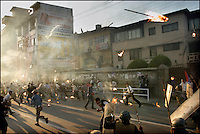 Protesters throw torches at charging police in Kathmandu, Nepal on 29 April, 2004. Weeks of clashes between police and protesters calling on the king to reinstate democracy lead to thousands of arrests and hundreds injured.<br />