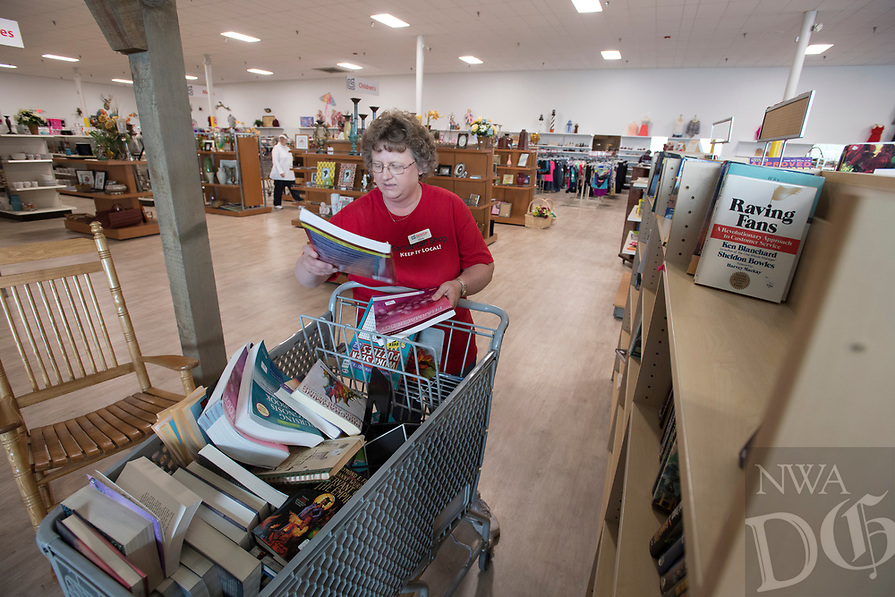 NWA Democrat-Gazette/J.T. WAMPLER Alicia Barrett of Rogers sorts books Thursday April 13, 2017 at Rogers Samaritan Shop's new location at the old Rogers Outdoor Sports location at 2115 W. Walnut in Rogers. The store has had record sales days since opening last Saturday.
