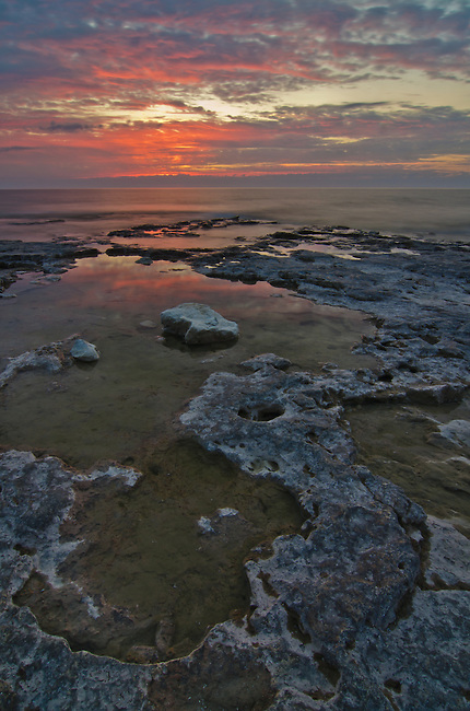 The sun rises into a sky beginning to fill with clouds over the Cave Point County Park shore of Lake Michigan in Door County, Wisconsin