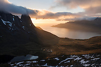 Midnight sun over Kongen mountain peaks and Øyfjord, Senja, Norway