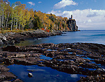 Split Rock Lighthouse State Park, MN  <br /> Clouds and blue sky reflect in small pools on the rocky shoreline of Lake Superior with fall forests and Split Rock Lighthouse in the distance