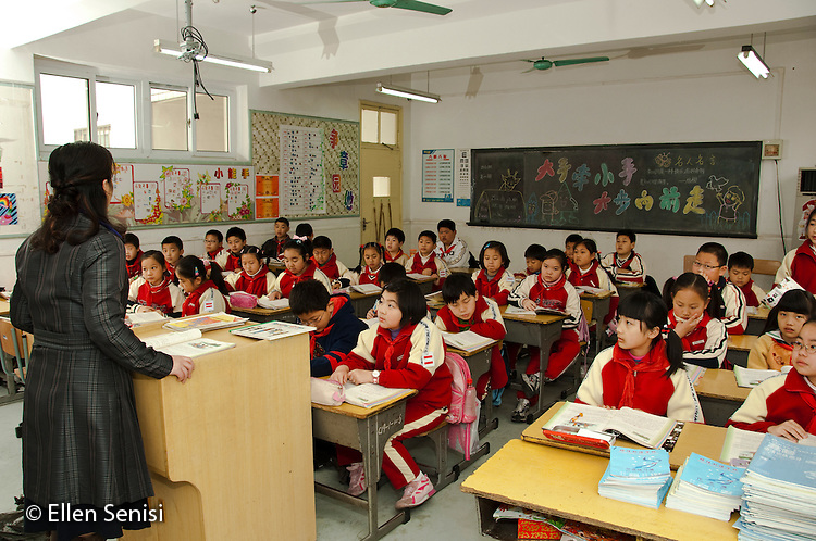 Shanghai, China. Peijia International School. Private school Kindergarten - High School. Many Students live here throughout the week. Grade 4. Teacher instructing Chinese literacy lesson to her class. Students are wearing uniforms with jackets and teacher wears a coat because space heaters are rarely turned on. ©Ellen B. Senisi