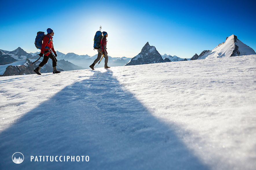 Three hikers climbing the final section of ridge to the summit of the Tete Blanche, a small, easy peak on the morning of the fifth day of the Chamonix to Zermatt Glacier Haute Route. In the distance is the Matterhorn.