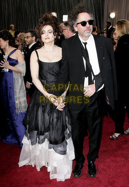 Helena Bonham Carter (wearing Vivienne Westwood) & Tim Burton.85th Annual Academy Awards held at the Dolby Theatre at Hollywood & Highland Center, Hollywood, California, USA..February 24th, 2013.oscars full length black white grey gray sleeveless dress asymmetrical tiered suit sling arm injury wound sunglasses shades couple holding hands beard facial hair .CAP/ADM.©AdMedia/Capital Pictures.