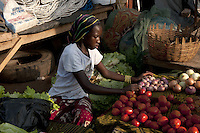 Young girl selling tomatos and onions at the market