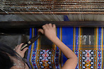 A woman operates a traditional loom to weave cloth in Kalay, a town in Myanmar.