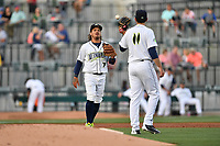 Third baseman Jay Jabs (7) of the Columbia Fireflies tosses the ball to starting pitcher Colin Holderman (11) to start the second inning of a game against the Lexington Legends on Saturday, April 22, 2017, at Spirit Communications Park in Columbia, South Carolina. Lexington won, 4-0. (Tom Priddy/Four Seam Images)