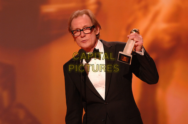 "BILL NIGHY.Accepts the award for Best Performance by an Actor In A Mini-Series Or A Motion Picture Made For Television for ""Gideon's Daughter"".Telecast - 64th Annual Golden Globe Awards, Beverly Hills HIlton, Beverly Hills, California, USA..January 15th 2007.globes stage half length tuxedo trophy microphone.CAP/AW.Please use accompanying story.Supplied by Capital Pictures.© HFPA"" and ""64th Golden Globe Awards"""