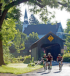 Cyclists participating in the Deerfield Dirt-Road Randonnee (D2R2) pedal through the Burkeville Covered Bridge in Conway, Mass., on Saturday, August 22, 2015. Photo by Christopher Evans