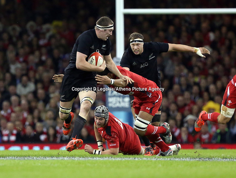 Pictured: Brodie Retallick of New Zealand (with ball) is brought down by Dan Lydiate of Wales Saturday 22 November 2014<br /> Re: Dove Men Series 2014 rugby, Wales v New Zealand at the Millennium Stadium, Cardiff, south Wales, UK.