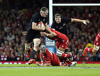 Pictured: Brodie Retallick of New Zealand (with ball) is brought down by Dan Lydiate of Wales Saturday 22 November 2014<br />