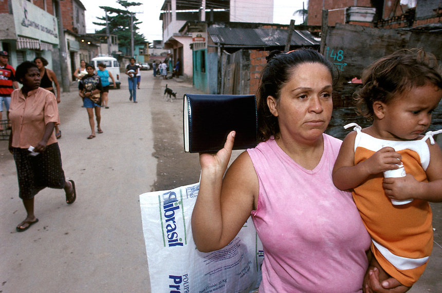 Maria José da Silva marches through the dirt streets of Rio's Vigário Geral slum armed with a bible, a granddaughter, and a bag of clothes she sells door-to-door to make her living. Da Silva was abandoned by her husband years earlier and sank into depression and alcoholism before she found hope in an evangelical church.