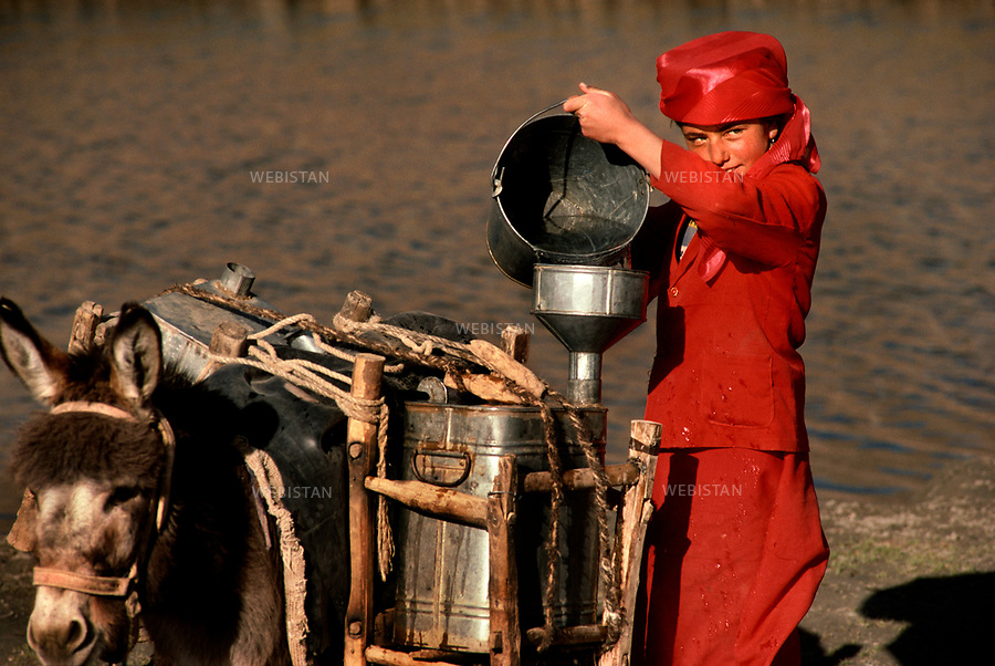 1995. Near Taxkorgan, a young Tajik girl pours the water in buckets carried by her donkey. Près de Taxkorgan, une fillette tadjike verse l'eau qu'elle vient de puiser dans les seaux transportés par son âne.