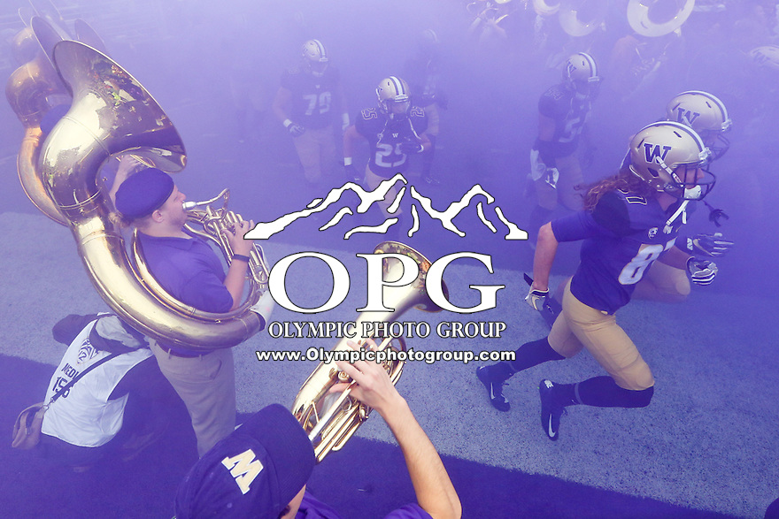 03 September 2016:  University of Washington players run between Washington band members through a cloud of purple smoke at the start of the game against Rutgers.  Washington defeated Rutgers 48-13 at the University of Washington in Seattle, WA.