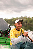 BRAZIL, Agua Boa, fishing guide sitting in a boat with a paddle, Agua Boa River and resort