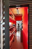 A view into a built-in storage room painted in a bold, bright red with plenty of shelving space. A woman stands at the far end.