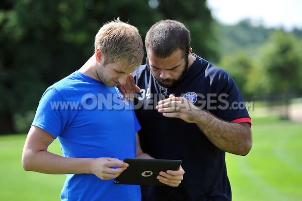 Performance Analyst Aled Griffiths shows some footage to Kane Palma-Newport after a scrummage session. Bath Rugby training session on August 27, 2013 at Farleigh House in Bath, England. Photo by: Patrick Khachfe/Onside Images