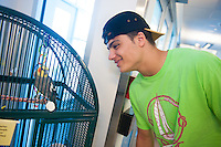 Jared Tirocchi,'19, says hello to Tuki, as he volunteers at the Potter League For Animals in Middletown as part of the Salve Regina community service project.