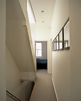 The narrow staircase landing has a suspended wire security screen and a view towards the master bedroom