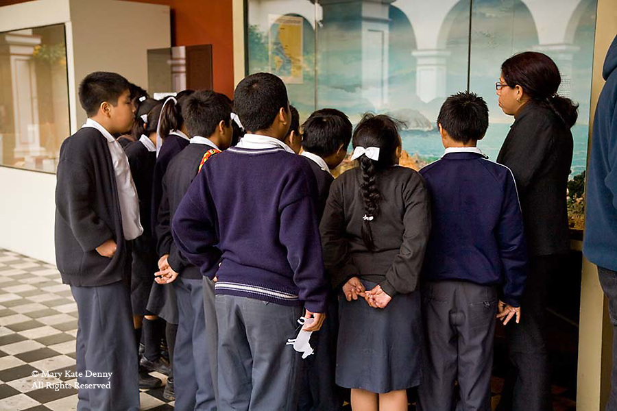 School children in uniforms observe historical exhibit at museum with teacher in Lima, Peru with backs to camera