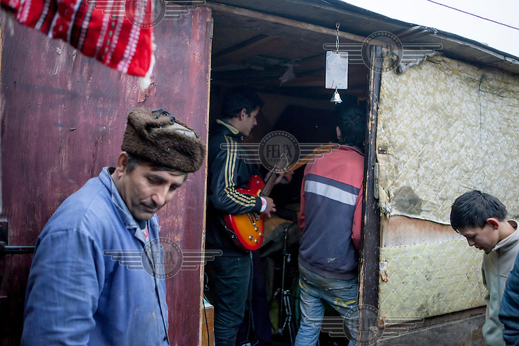 A man stands outside a hut wear a band is playing in the Roma settlement located in 'Budulovskej Street'.