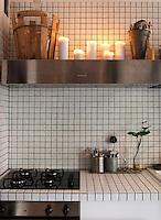 Lit candles above the extractor bring a warm golden glow to this corner of the kitchen