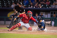 Northwest Arkansas Naturals infielder Angelo Castellano (16) (right) slides safely into home for a run ahead of the tag attempt from Springfield Cardinals catcher Jose Godoy (27) on May 18, 2019, at Arvest Ballpark in Springdale, Arkansas. (Jason Ivester/Four Seam Images)