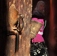 Wooden door suddenly opened and revealing a girl with scarf, flashy pink duffle-coat and black velvet skirt at Ksar Ait Ben Haddou, earthen fortified city, Ounila valley, Ouarzazate province, Morocco. The ksar is a group of earthen houses surrounded by high defensive walls with corner towers, in traditional pre-Saharan style.  The village stands above the Oued Marghen river in the High Atlas and was a stop on the caravan route from the Sahara to Marrakech. It was founded in the 17th century and has been a UNESCO World Heritage Site since 1987. Picture by Manuel Cohen