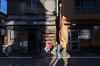 Elementary school girls walk home from school in Yutenji, Tokyo, Japan. Friday November  27th 2015