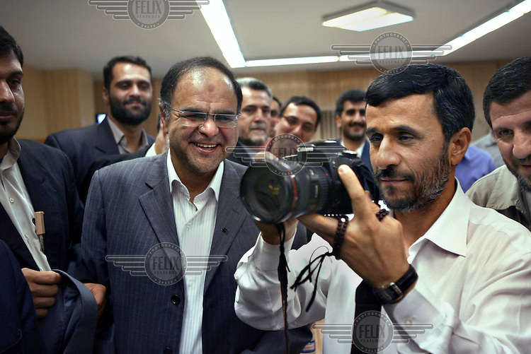 Iranian President Mahmoud Ahmadinejad uses a Canon 20D to take photographs of journalists working at the state-owned IRNA (Islamic Republic News Agency), during Iran's National Journalism Day.