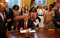 "United States President Donald J. Trump signs the National Security Presidential Memorandum to Launch the ""Women's Global Development and Prosperity"" Initiative in the Oval Office of the White House in Washington, DC on Thursday, February 7, 2019.<br /> Credit: Martin H. Simon / CNP/AdMedia"