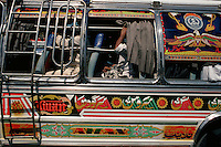 Passengers get little protection from the hot sun as they sit waiting for their bus to leave the bus terminal in Rawalpindi, Pakistan.