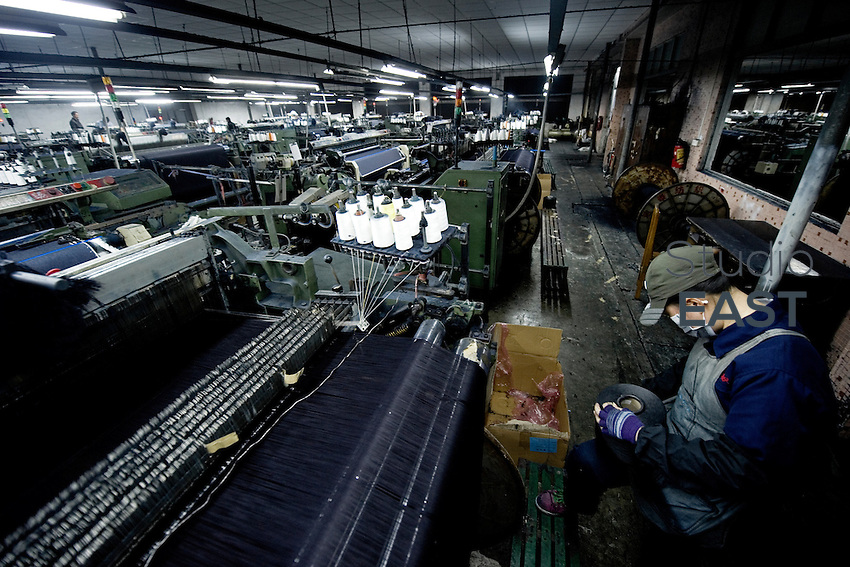 A worker supervises a power loom weaving denim to be used to manufacture blue jeans in LSH textile company, in Xintang, Guangdong province, China, on February 9, 2012. Photo by Lucas Schifres/Pictobank