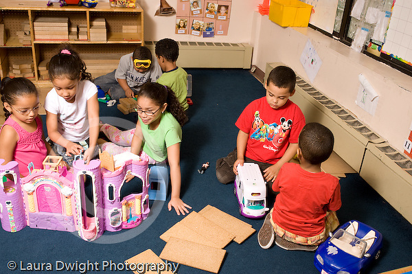 Preschool ages 3-5 separate groups of boys and girls playing near each other girls playing with doll house and boys with blocks, tools, and vehicles horizontal